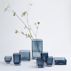 eight blue city herb glass vases in different sizes and shapes.