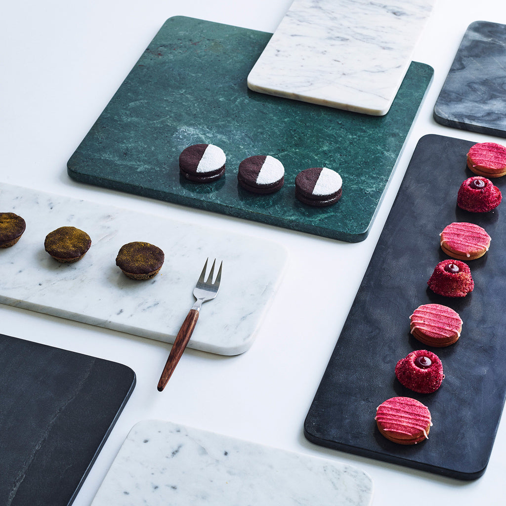 Multiple marble plates in green, black and white with delicious cakes on top.