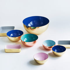 Metal bowls and trays in different colors and sizes.