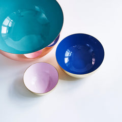 Three metal bowls in the colors light blue, blue and rose.