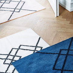 Two handwoven BORG wool rugs, one in royal blue and ecru with black graphic lines.