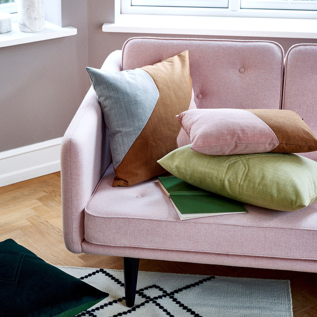 Little architect cushions in light colors on a pink sofa.