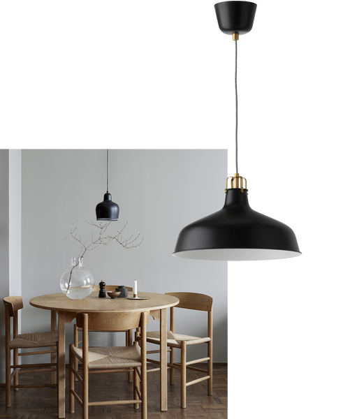 a minimal Scandi-style dining room with a round wooden table and a simple black pendant light above it