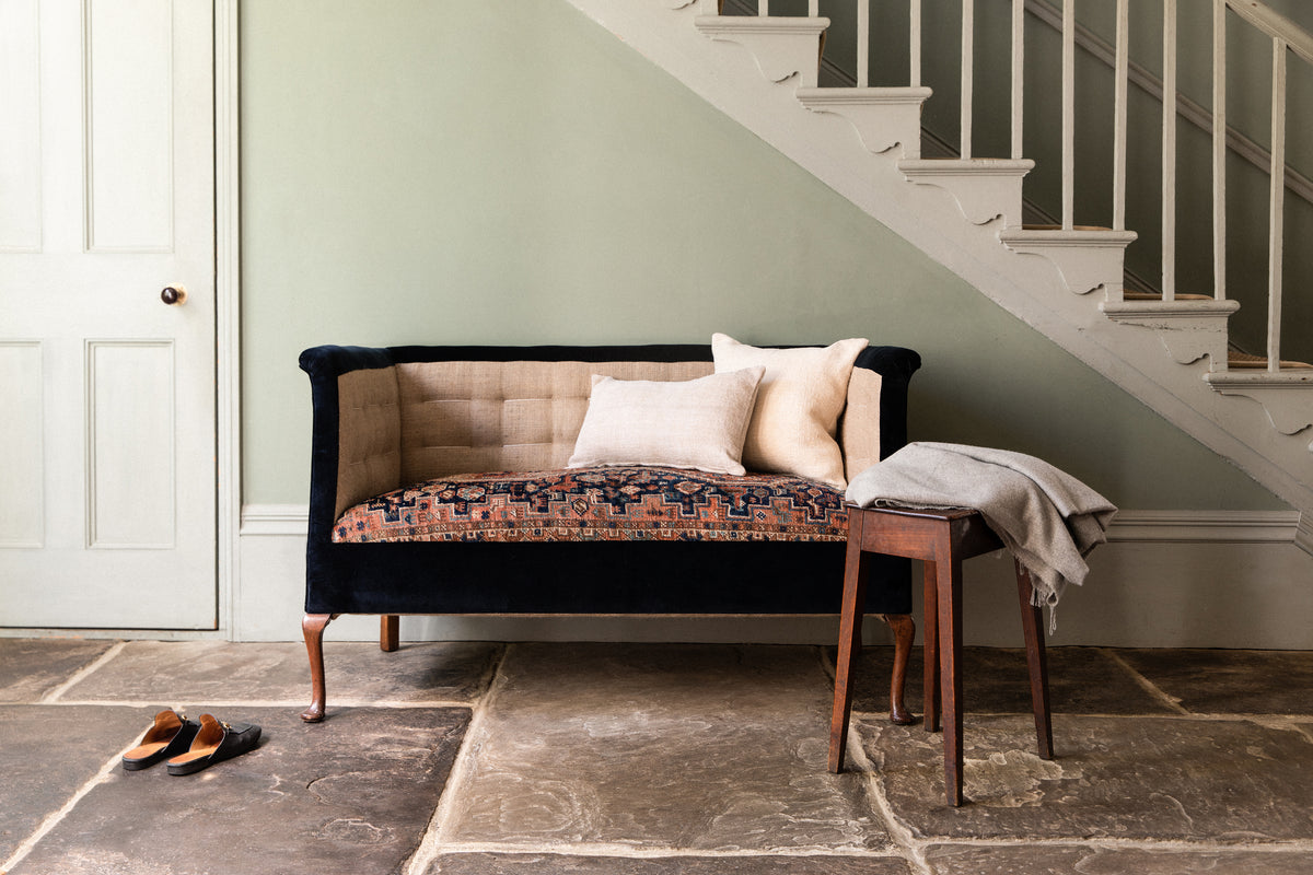 An antique sofa upholstered in midnight blue velvet with an antique rug cushion.