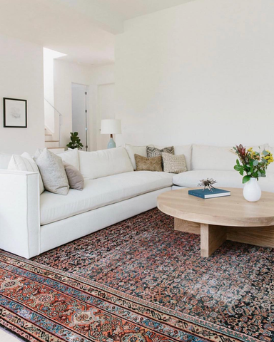 a large antique rug is the centrepiece, and a large white corner sofa sits on top