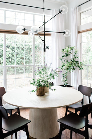 a circular dining table surrounded by floor to ceiling windows and lots of greenery