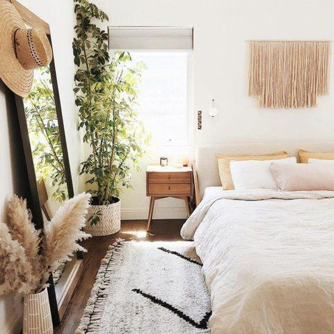 a bright, boho themed bedroom with a macramé wall hanging above the bed. A large Moroccan rug lies beneath the bed with a large mirror propped against the wall beside it