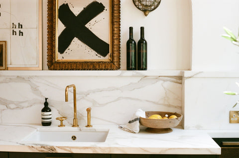 brass tap with marble splash back