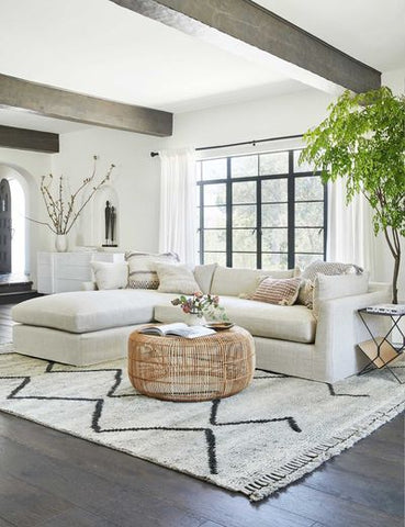 a large moroccan shag rug styled with a large white linen sofa and a wicker pouf