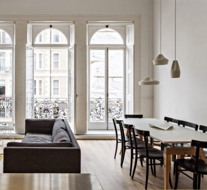 a large Victorian apartment with high ceilings, large windows and a big dining table