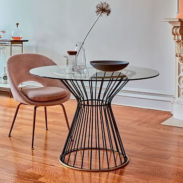 a round metal table with a pink chair beside it and a single flower in a vase