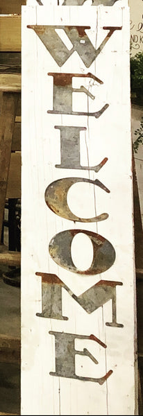 Old Tin Verticle Welcome sign on shiplap