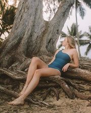 model wearing a one piece swimsuit relaxing on roots of a tree in Hawaii