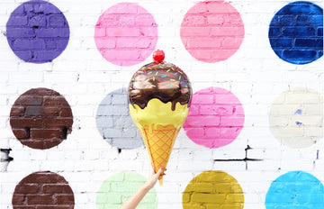 ice cream cone balloon in front of mural with colored dots