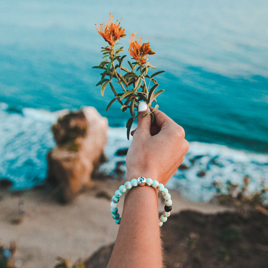 Woman holding flower wearing silicone beaded bracelet with seaweed and starfish on it.