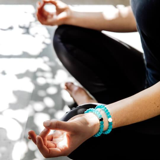 Woman sitting down doing yoga with stack of teal silicone beaded bracelets on wrist.