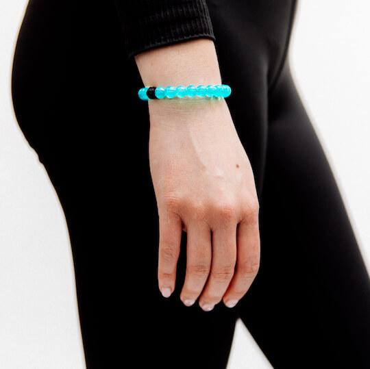 Woman wearing teal silicone beaded bracelet on wrist with hand hanging by her side.
