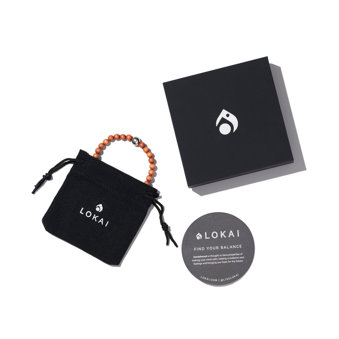 Wood bead bracelet with lokai symbol on either side insie of lokai packaging