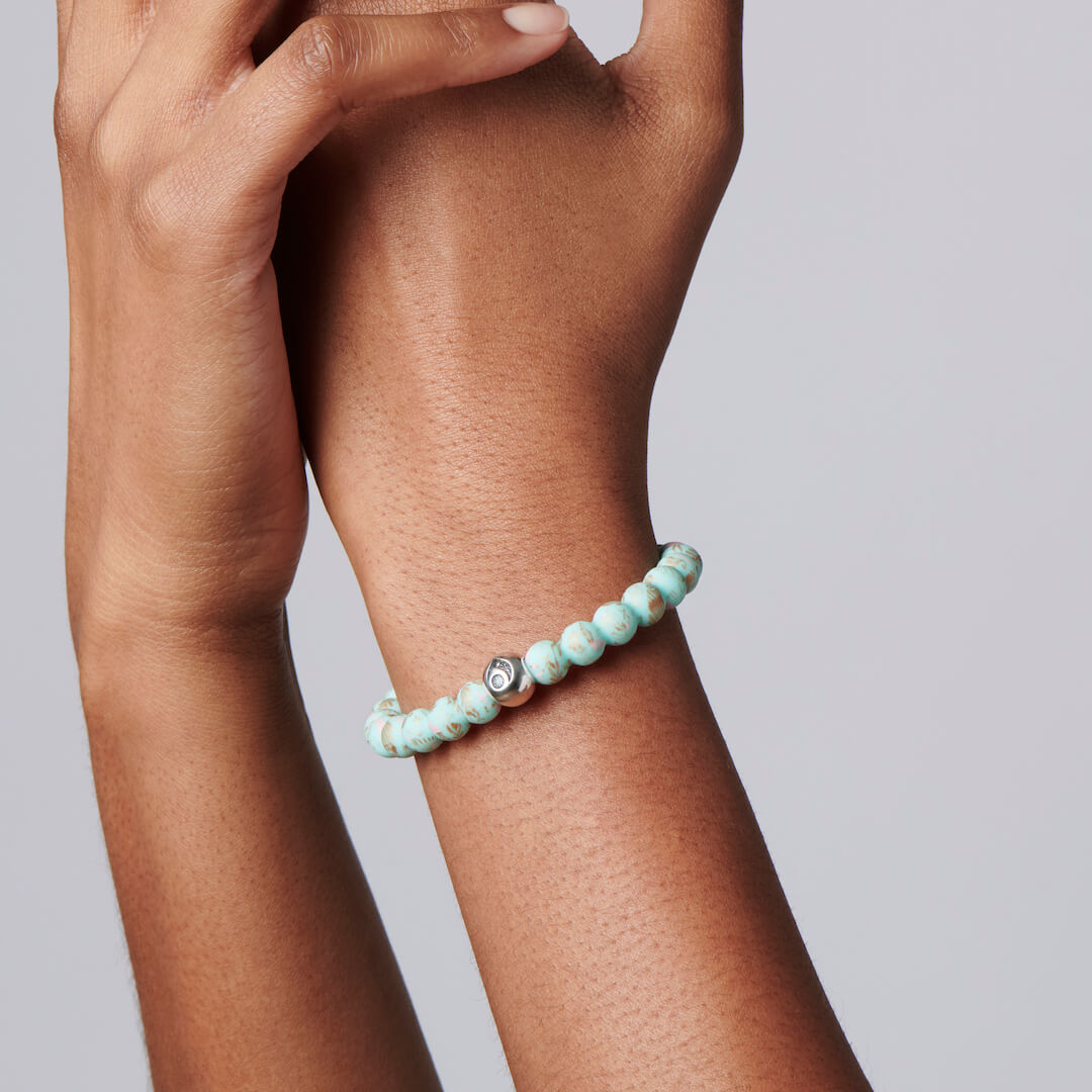 Woman wearing silicone beaded bracelet with seaweed and starfish on it.