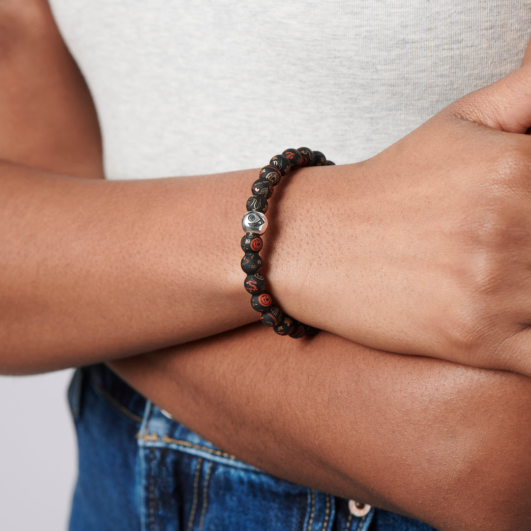 Woman crossing her arms, wearing silicone beaded bracelet with Mulan pattern.