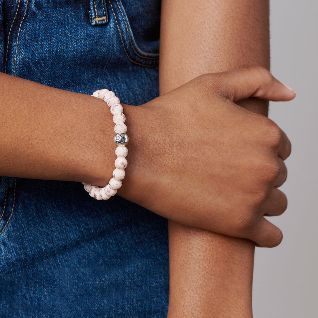 Woman holding her arm wearing a silicone beaded bracelet with Pocahontas pattern.