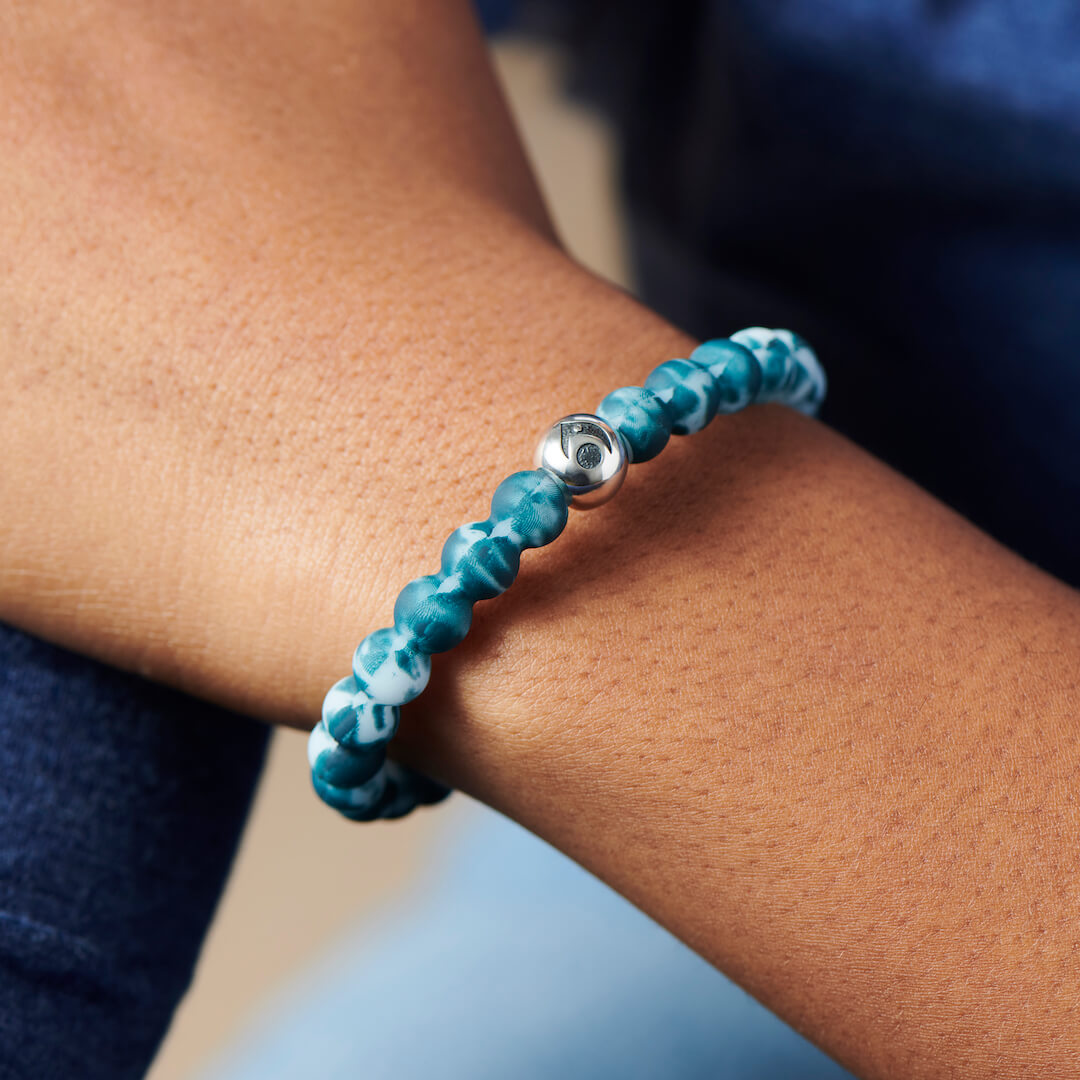 Woman wearing turquoise and light blue tie-dye silicone beaded bracelet.