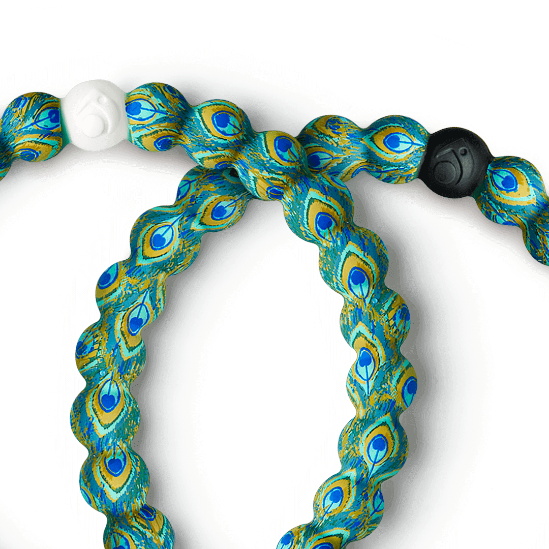 Close-up silicone beaded bracelet with peacock pattern on it.