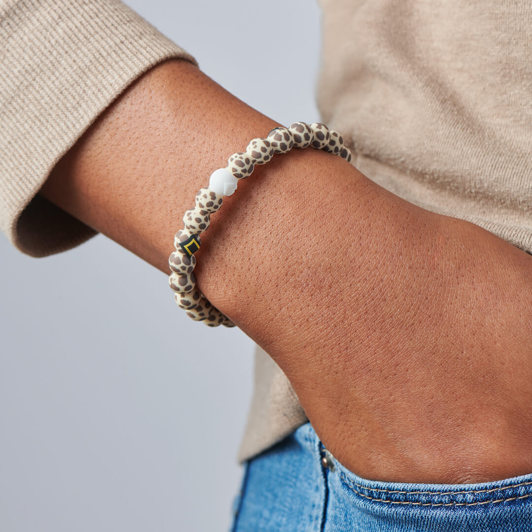 Person wearing silicone beaded bracelet with cheetah pattern on it.