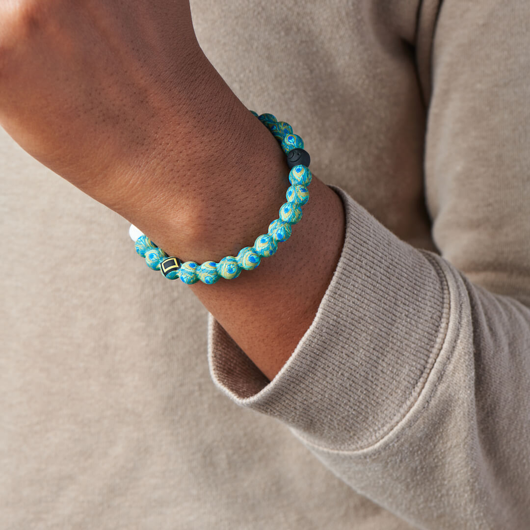 Person wearing silicone beaded bracelet with peacock pattern on it.