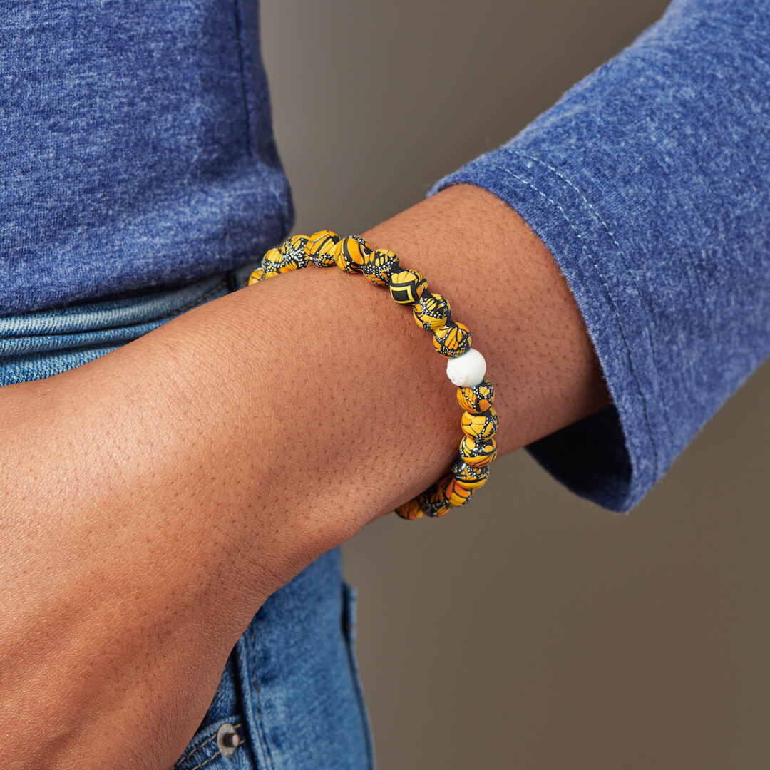 Person wearing silicone beaded bracelet with butterfly pattern on it.