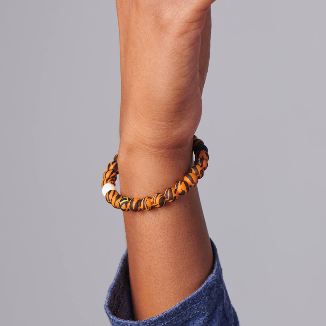 Person wearing silicone beaded bracelet with tiger pattern on it.