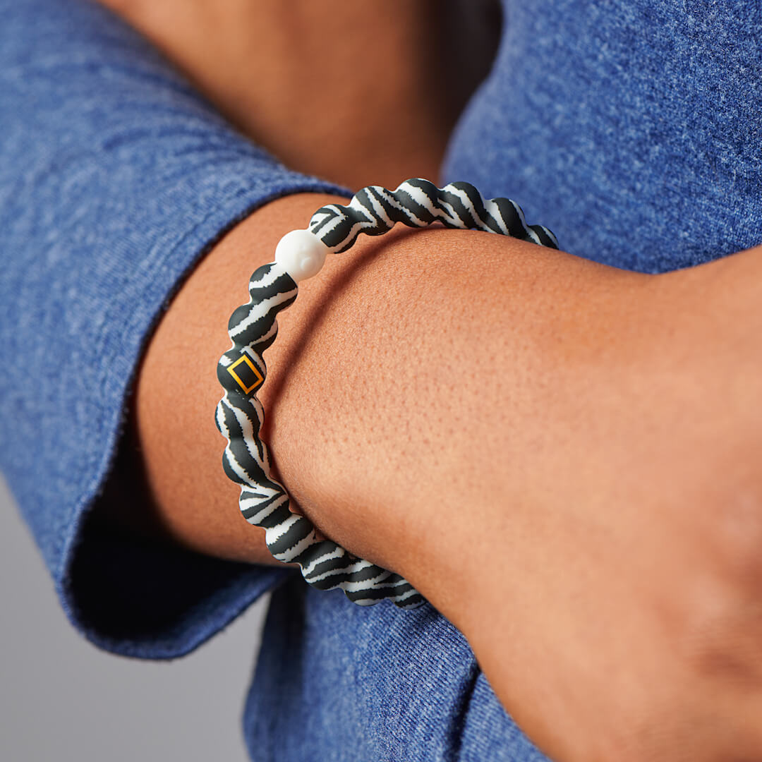 Person wearing silicone beaded bracelet with zebra pattern on it.