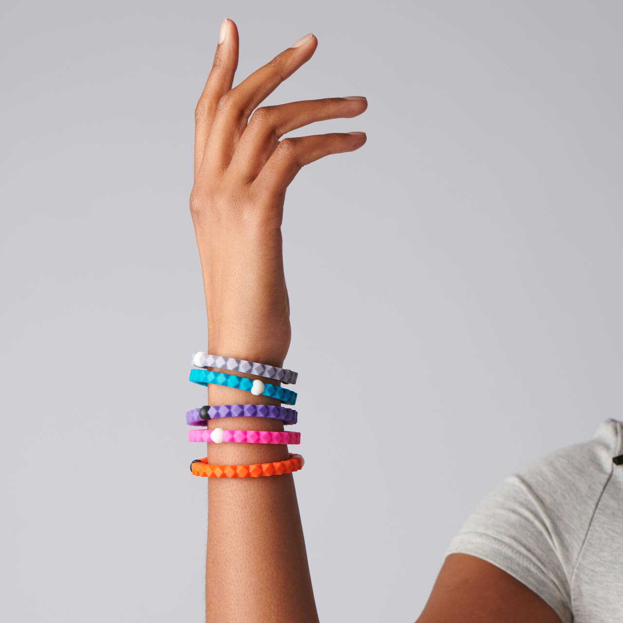 Woman wearing a collection of silicone hexagon shaped beaded bracelets