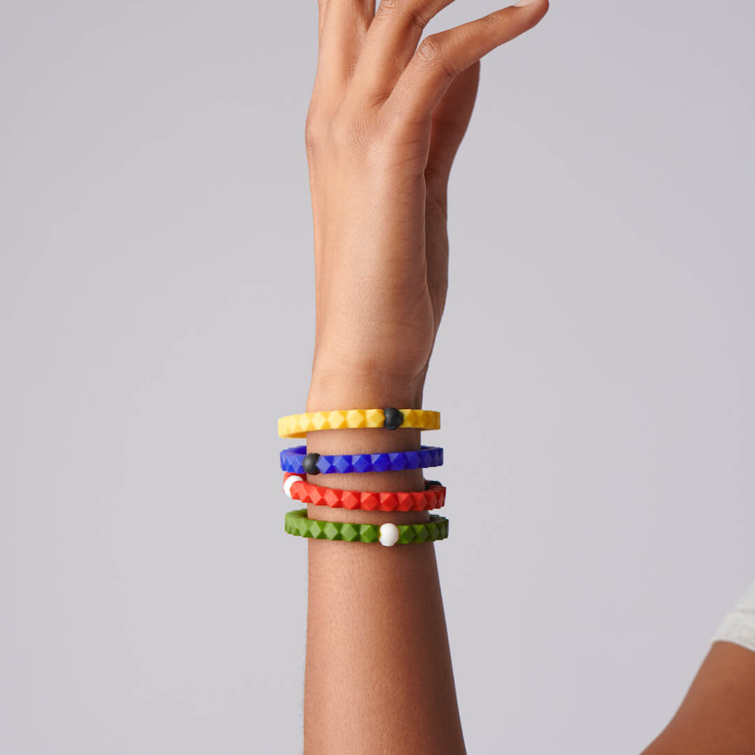 Woman wearing a collection of silicone hexagon shaped beaded bracelet