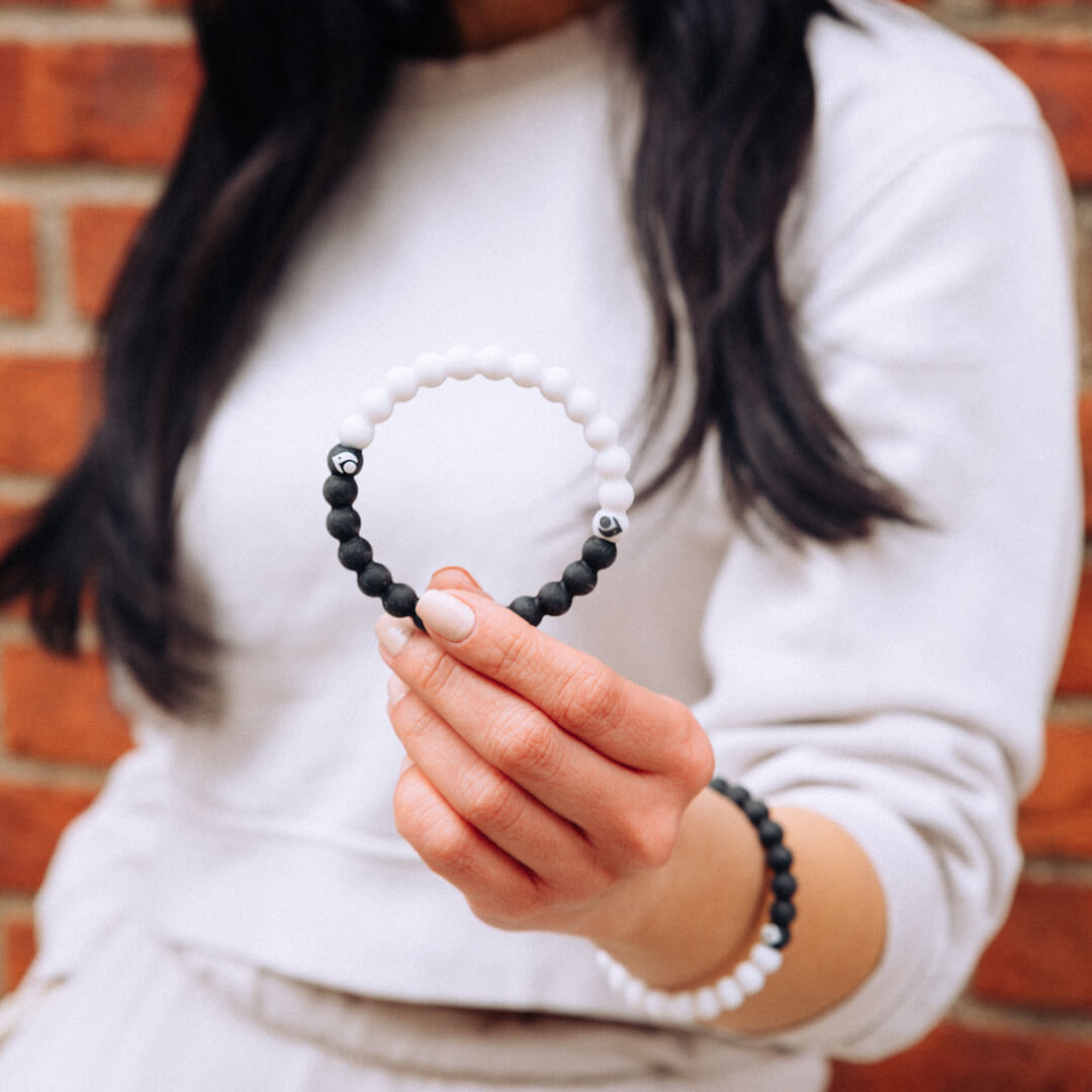 Woman holding a black and white silicone beaded bracelet.