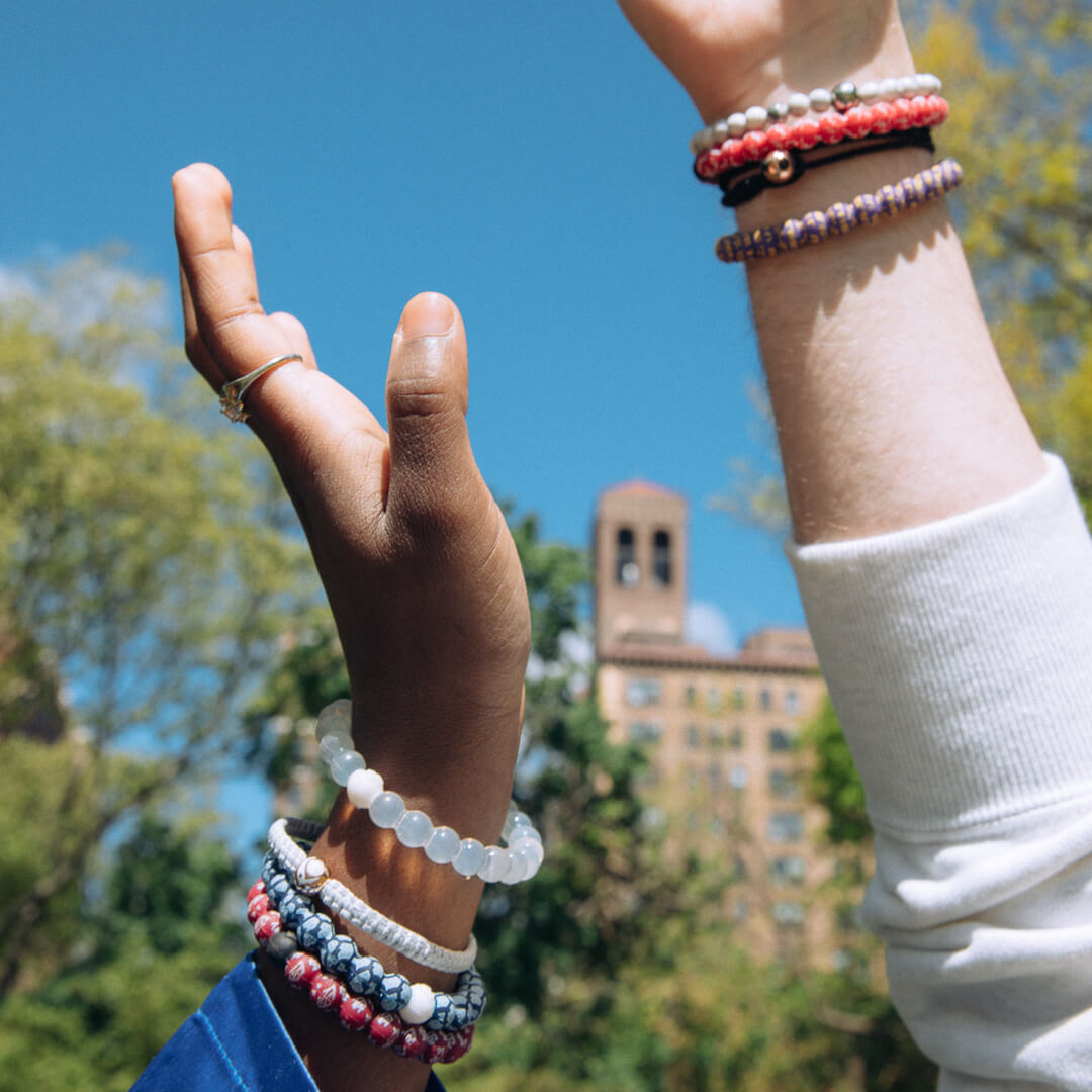 Two hands in the air wearing College logo lokai bracelets