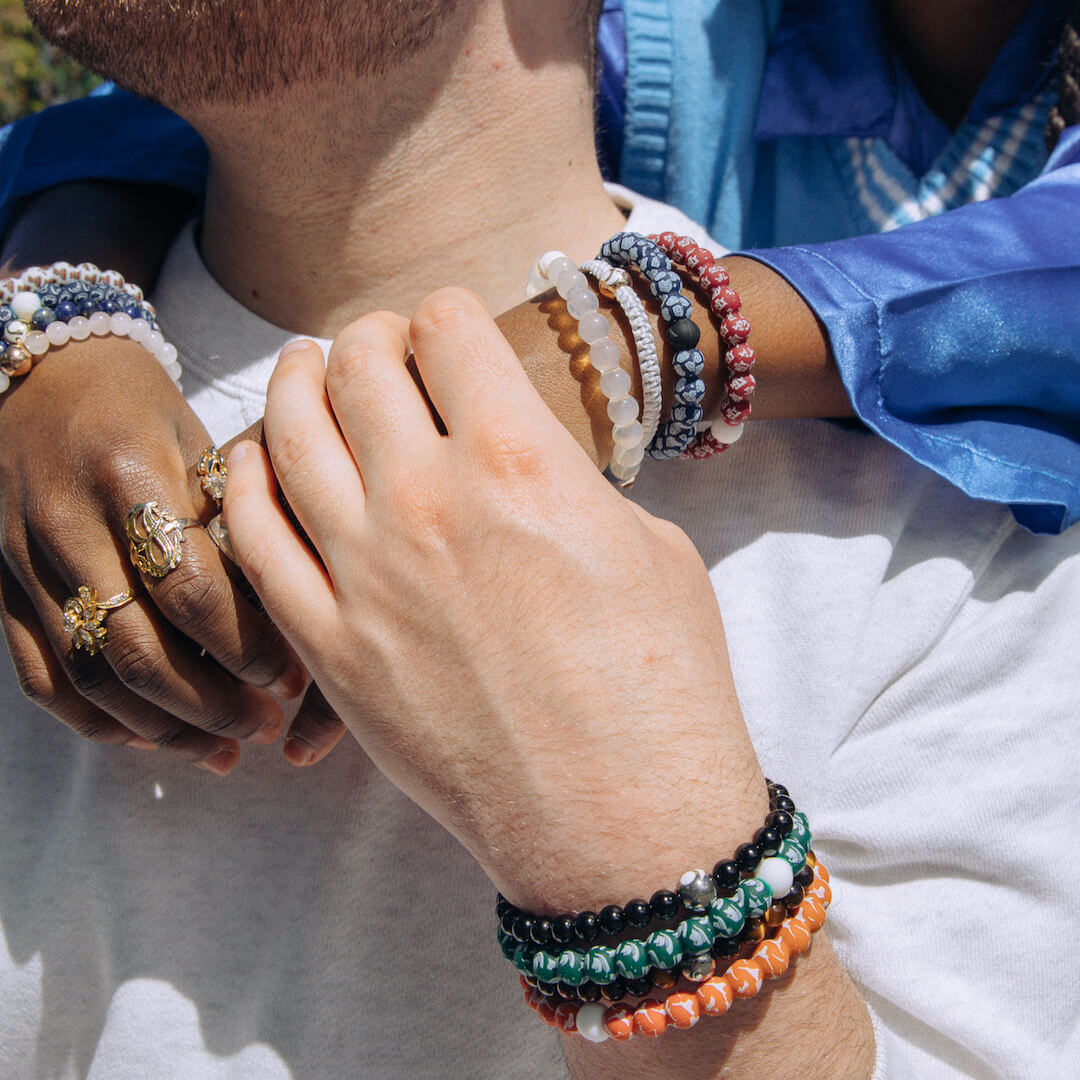 Woman and man holding hands wearing College logo lokai bracelets