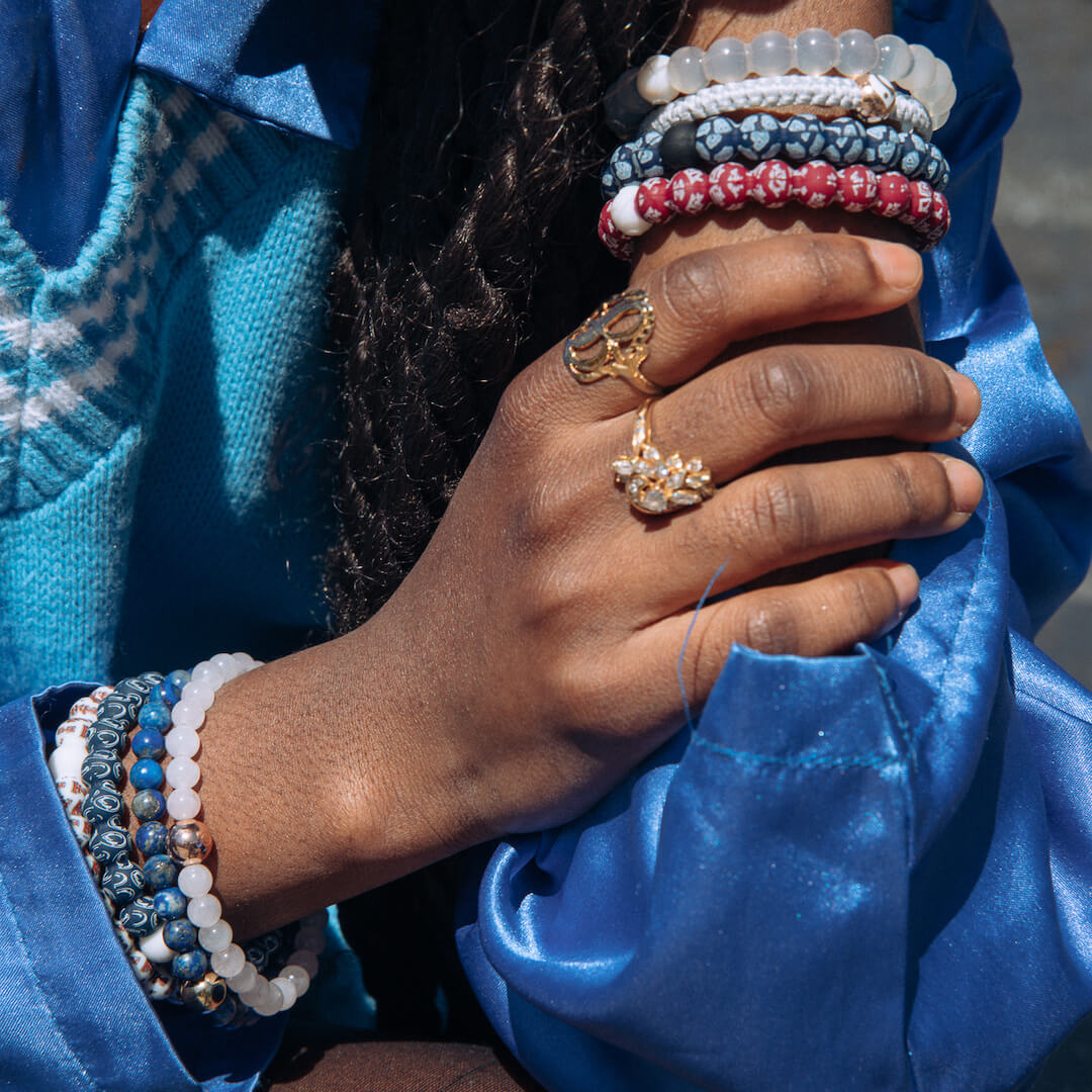 Woman holding her arm wearing a light blue and navy silicone beaded bracelet with the University of North Carolina logo pattern all over it.