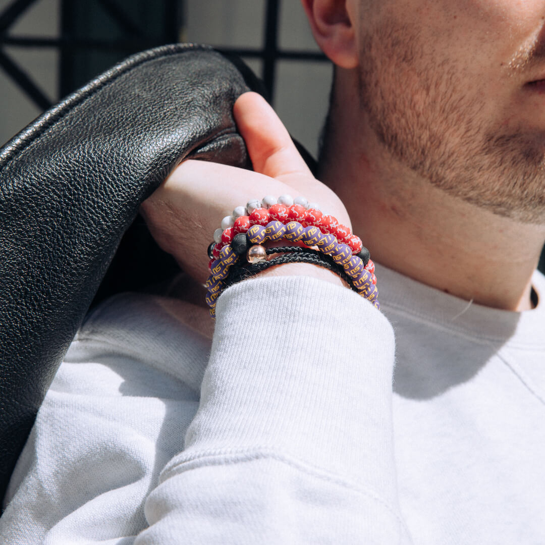 Man holding jacket wearing a yellow and purple silicone beaded bracelet with the Louisiana State University logo pattern all over it.