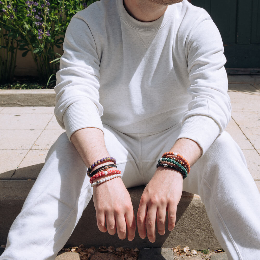 Man sitting on sidewalk wearing an orange and white silicone beaded bracelet with the University of Texas logo all over it.