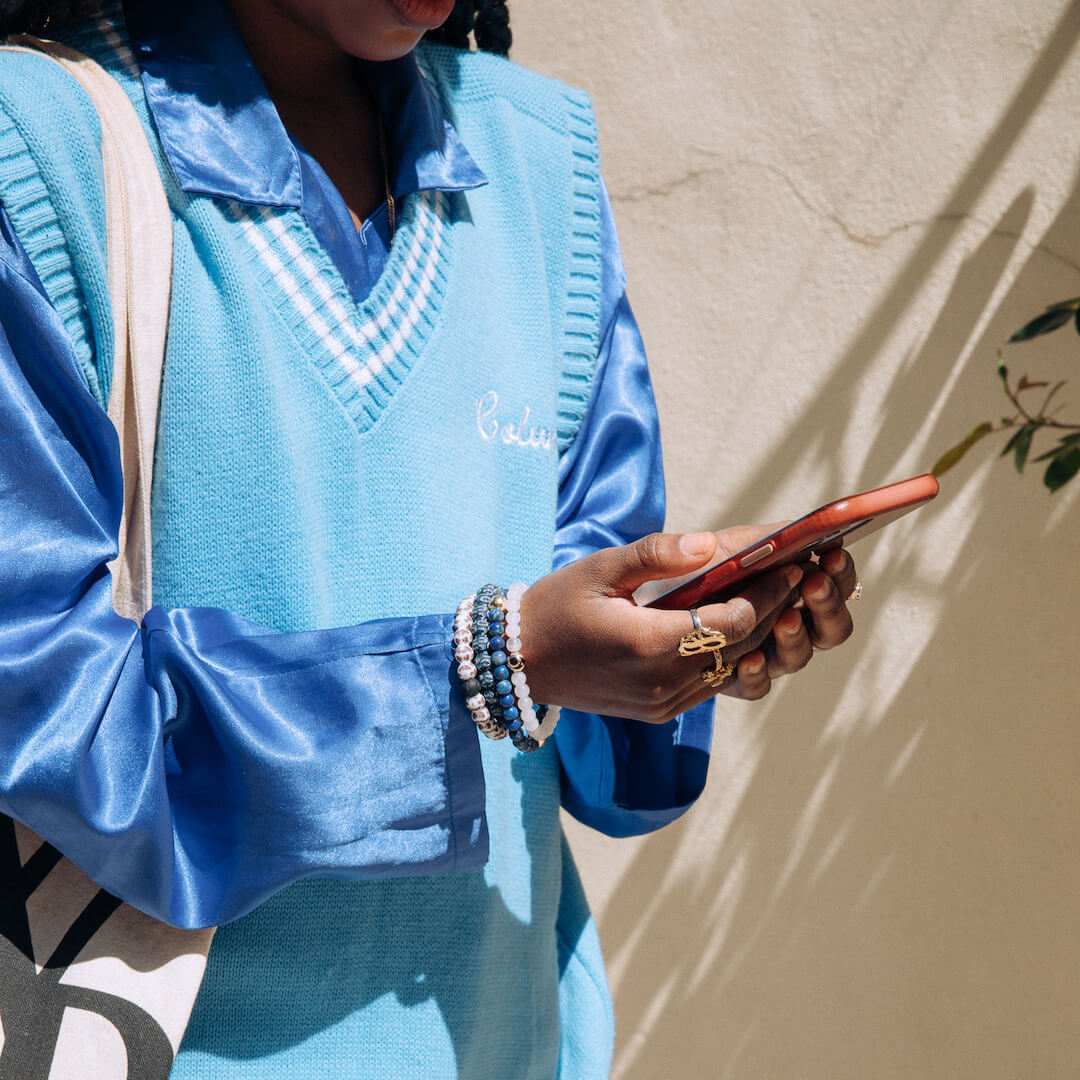 Woman with phone wearing College logo lokais