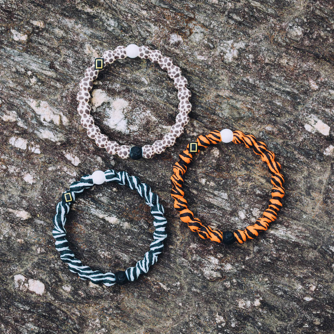 Zebra, tiger and cheetah pattern silicone beaded bracelets on a rock.