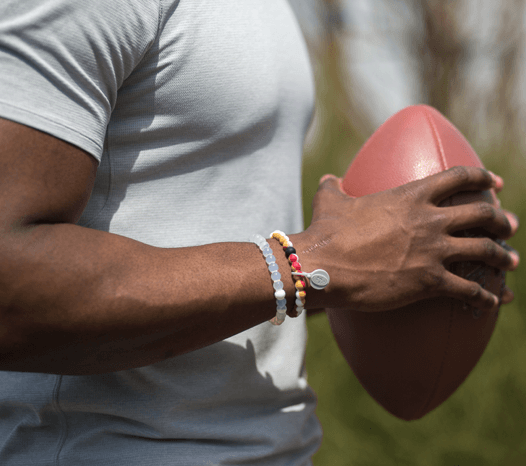 Male wearing a red, gold and white silicone beaded bracelet on wrist while holding a football.