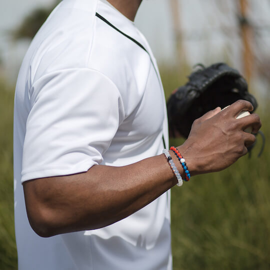 Male wearing black, blue and orange silicone beaded bracelet on wrist while holding a baseball.
