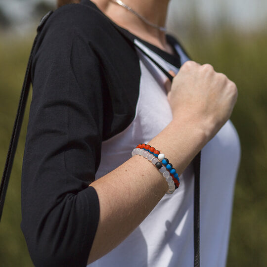 Woman wearing black, blue and orange silicone beaded bracelet while holding shoulder bag straps.