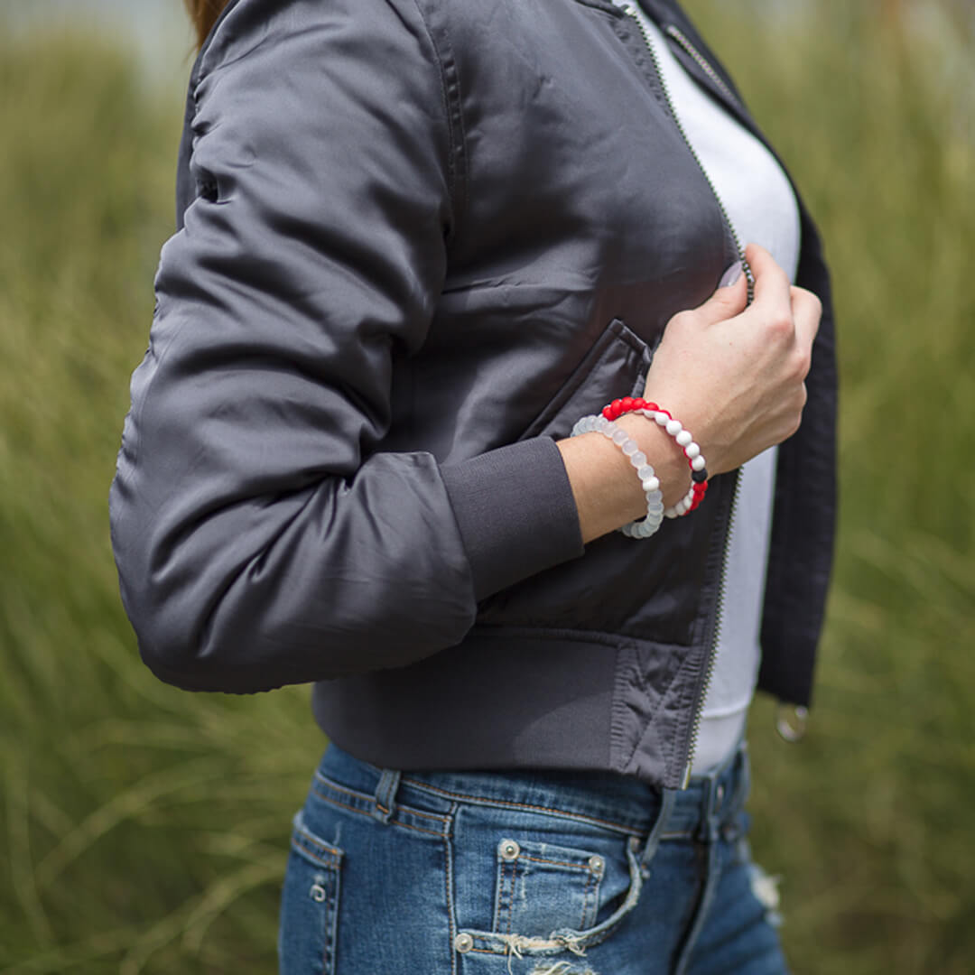 Woman wearing a gray bomber jacket with a red and white silicone beaded bracelet on wrist.