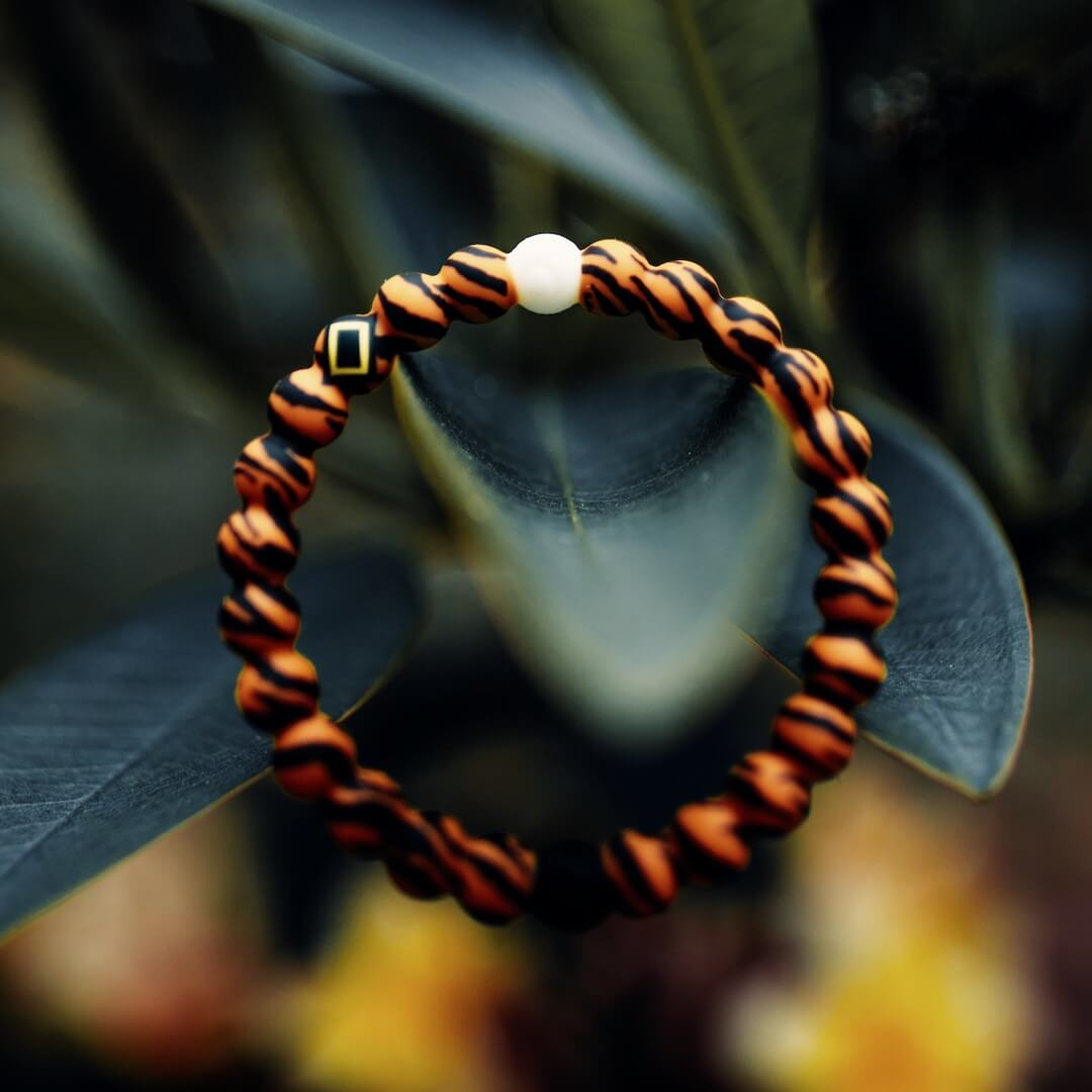 Silicone beaded bracelet with tiger pattern on it resting on a plant.