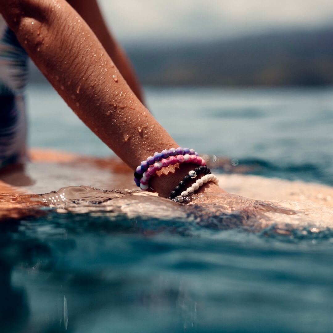 Woman on surfboard wearing Surf collection silicone beaded bracelets.