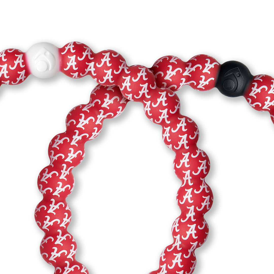 Close-up of red and white silicone beaded bracelet with the University of Alabama logo pattern.