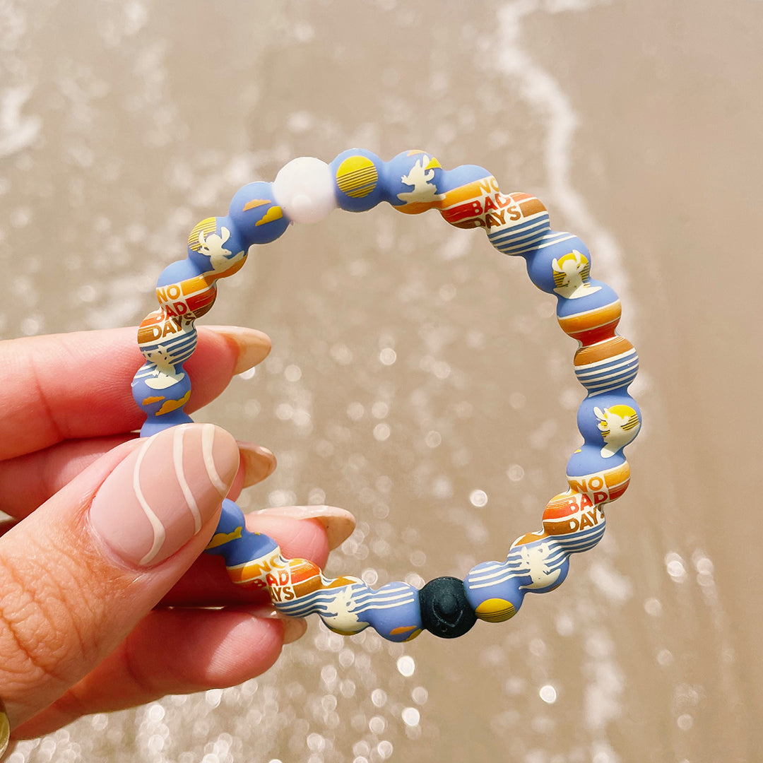 Close up of woman holding lilo and stitch bracelet on beach